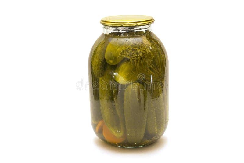 被隔绝的酱瓜 在玻璃瓶子的腌汁用在白色背景和干胡椒隔绝的大蒜 库存照片