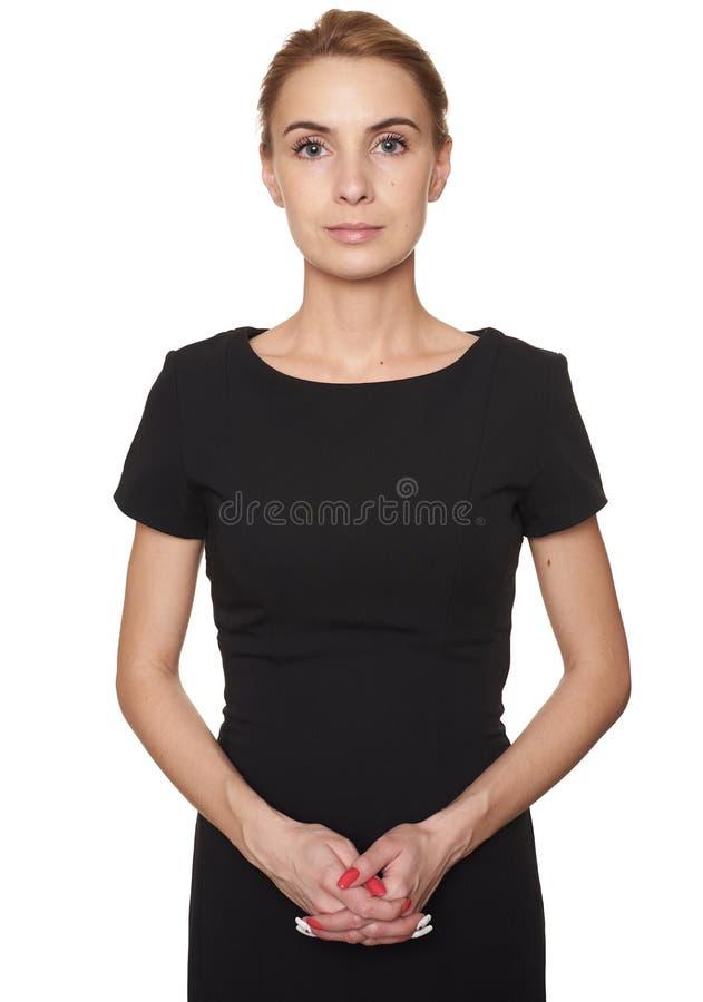被隔绝的黑礼服的美丽的年轻女人 免版税库存图片