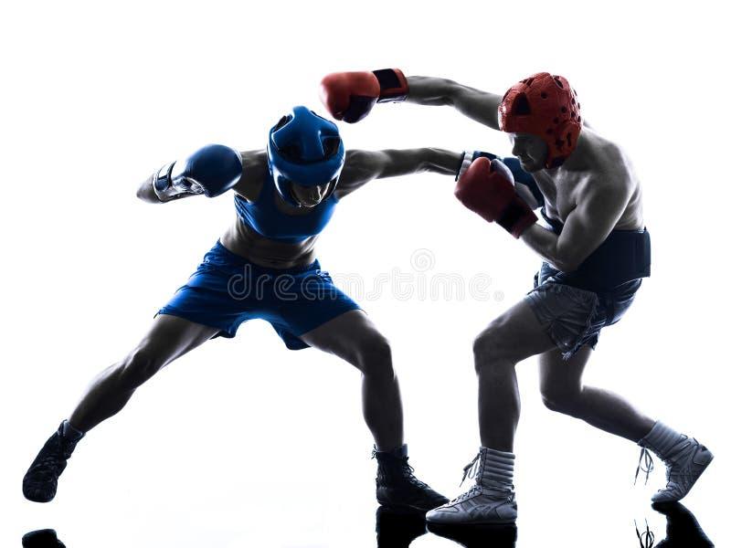 被隔绝的妇女拳击手拳击人kickboxing的剪影 图库摄影