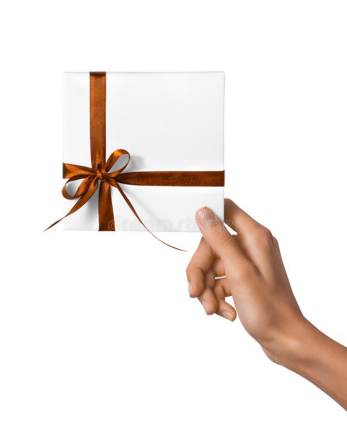 被隔绝的妇女递拿着有橙黄色丝带的假日当前白色箱子在白色背景 免版税库存图片
