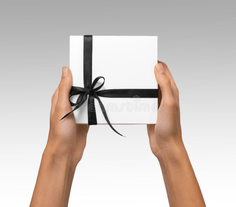 被隔绝的妇女递拿着有深黑色丝带的假日当前白色箱子在白色背景 免版税库存图片