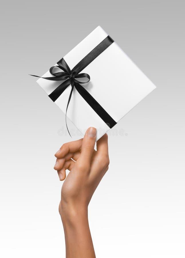 被隔绝的妇女递拿着有深黑色丝带的假日当前白色箱子在白色背景 库存图片