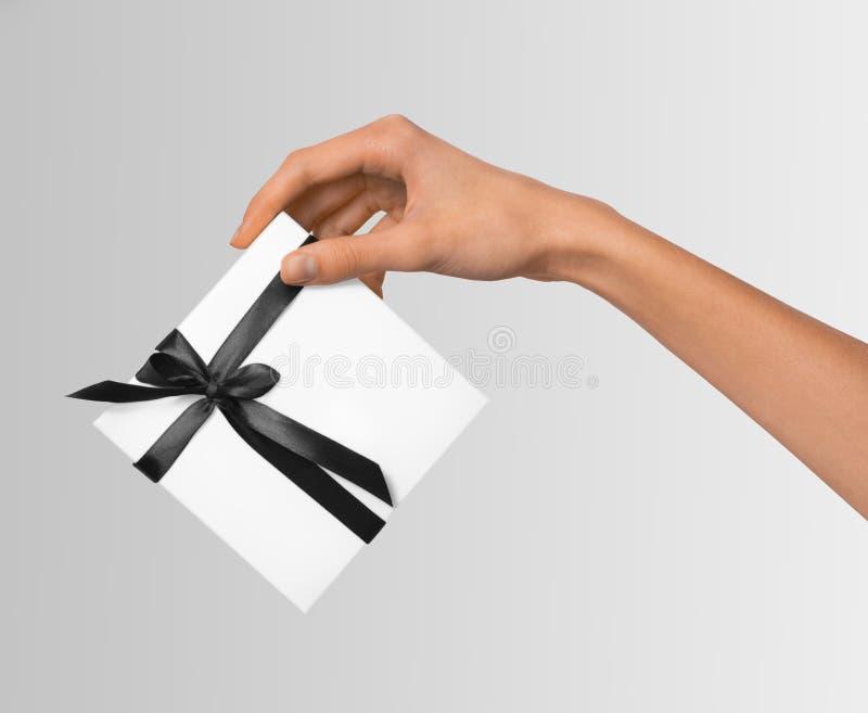 被隔绝的妇女递拿着有深黑色丝带的假日当前白色箱子在白色背景 库存照片