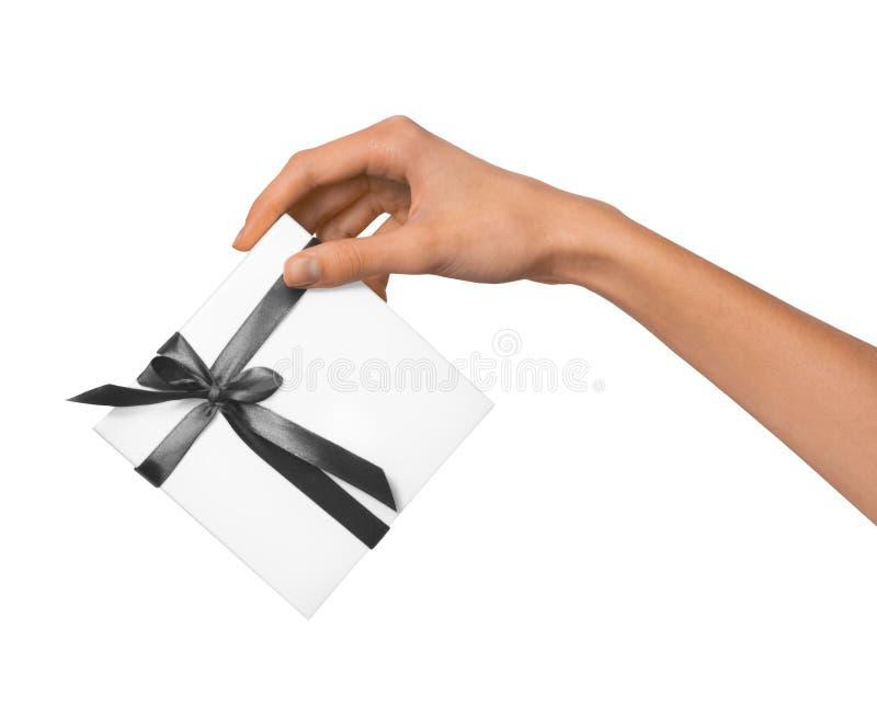 被隔绝的妇女递拿着有灰色丝带的假日当前白色箱子在白色背景 免版税图库摄影