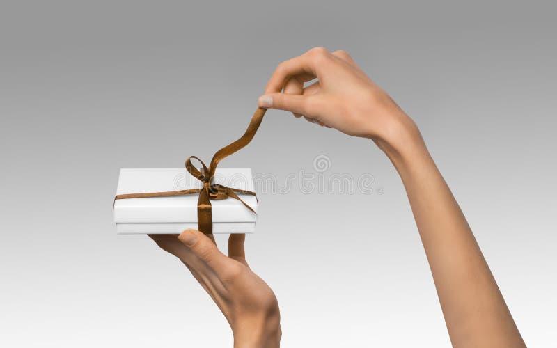 被隔绝的妇女递拿着有眉头的假日当前白色箱子 免版税库存图片