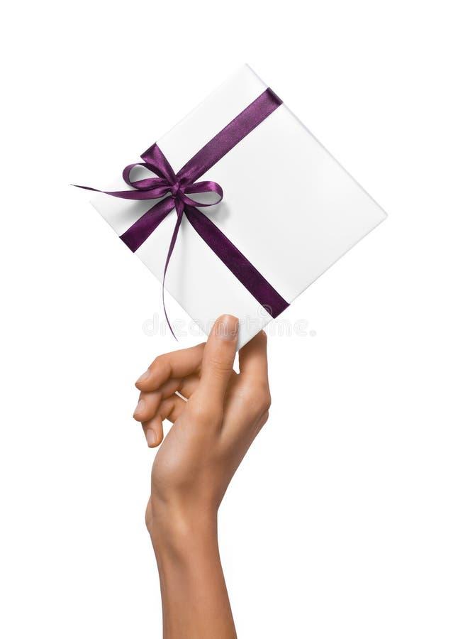 被隔绝的妇女递拿着有紫色丝带的假日当前白色箱子在白色背景 免版税库存图片