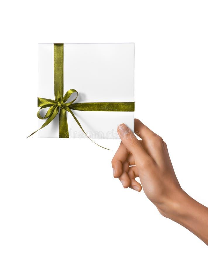 被隔绝的妇女递拿着有黄绿色丝带的假日当前白色箱子在白色背景 免版税库存照片