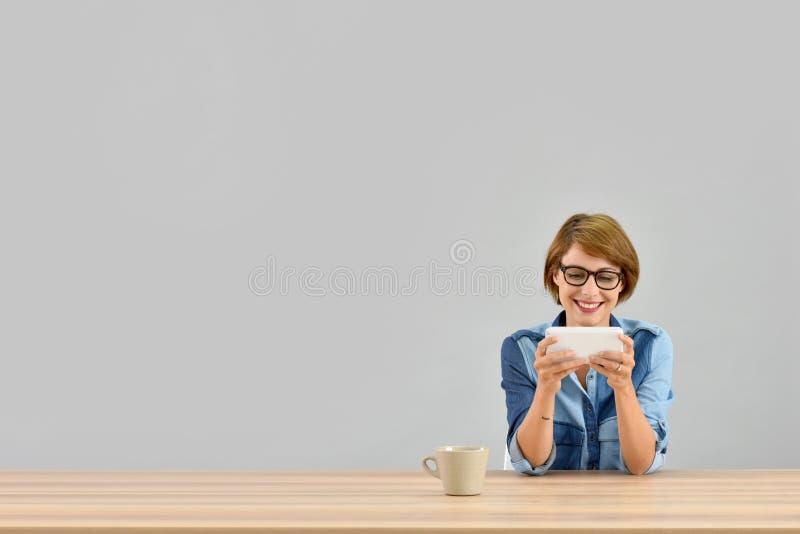 被隔绝的少妇佩带的镜片woth智能手机 免版税库存图片