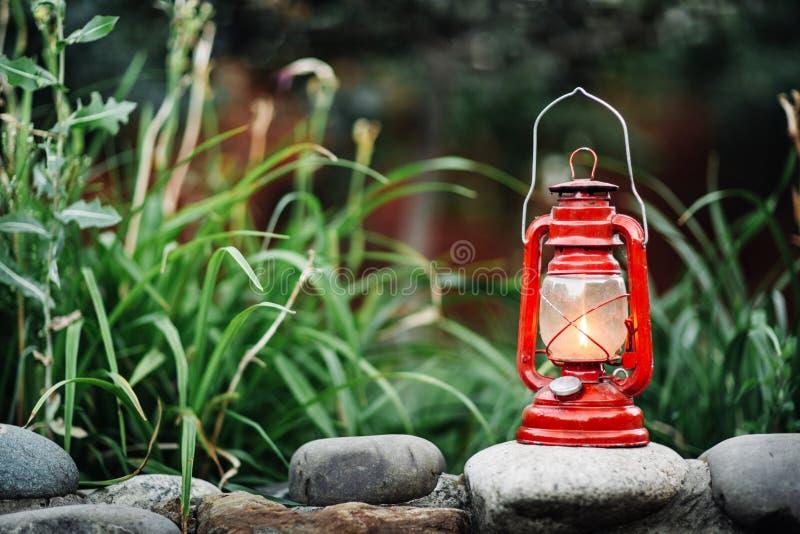 被隔绝的红色煤油灯在庭院背景 免版税库存照片