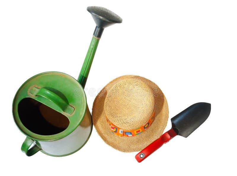 被隔绝的绿色庭院喷壶、草帽和铁锹 库存图片