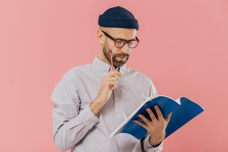 被集中的不剃须的成人人拿着蓝色课本,并且铅笔,读必要的信息,有严肃的表情,佩带 免版税库存图片