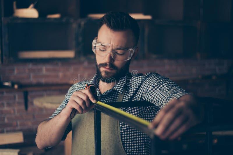 被集中的严肃的英俊的有胡子的专业佩带的检查 免版税库存图片