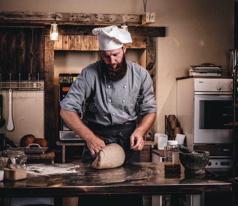 被集中的厨师揉的面团在厨房里 免版税图库摄影