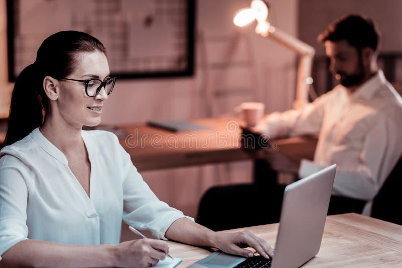 被集中的可靠同事坐和与膝上型计算机一起使用 免版税库存照片