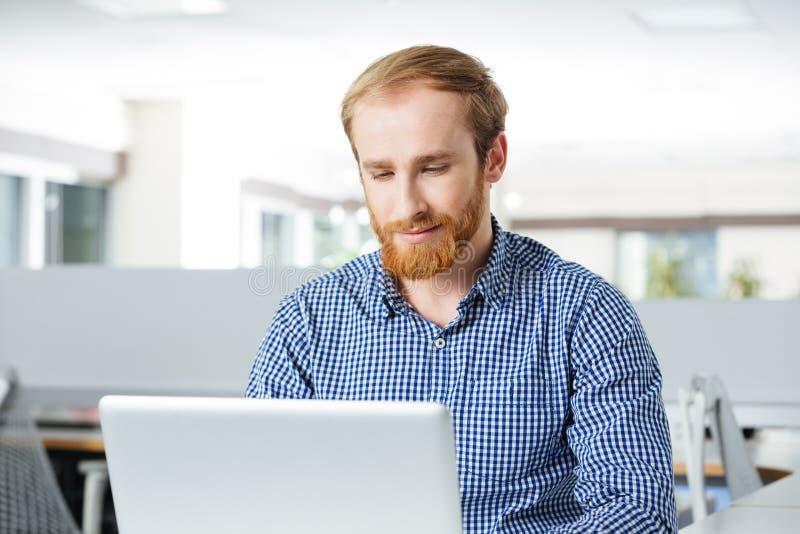 被集中的商人与膝上型计算机一起使用在办公室 免版税库存图片