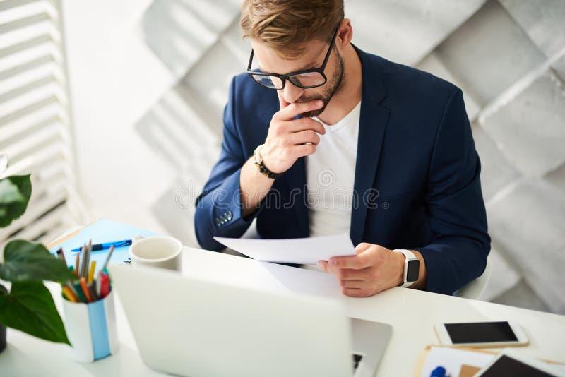 被集中的商人读书文件在办公室 免版税库存图片