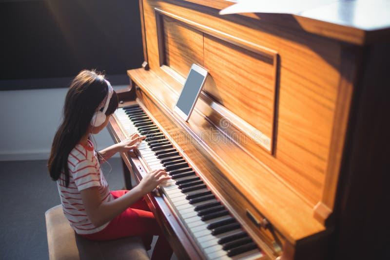 被集中的女孩实践的钢琴大角度看法  图库摄影