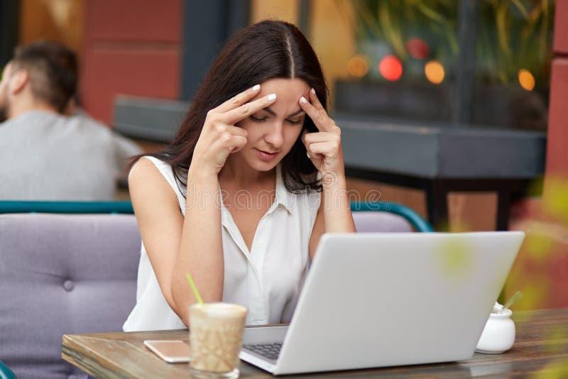 被集中的女性新闻工作者尝试对focuse当creats新的文章,在现代便携式计算机前面坐在自助食堂, surrou 免版税图库摄影