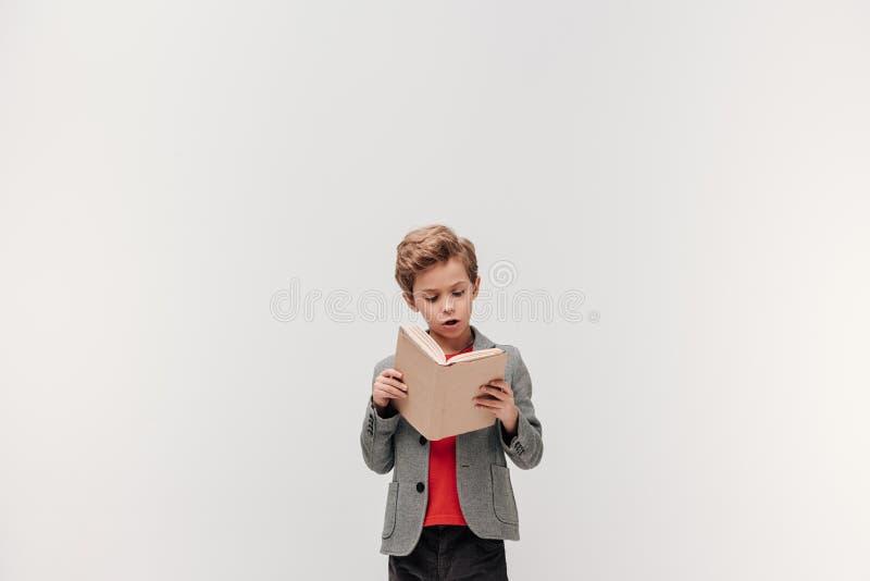 被集中的小的男小学生阅读书 图库摄影