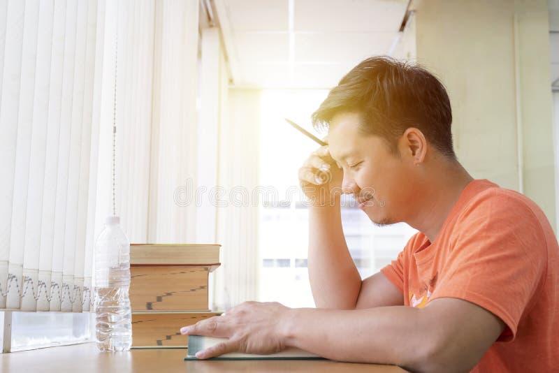 被集中的年轻人读一本书,坐在桌和wr上 免版税图库摄影