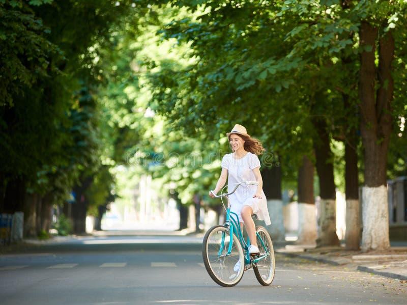 被集中的微笑的女性,当骑蓝色自行车在宽绿色街道中间时 免版税库存图片