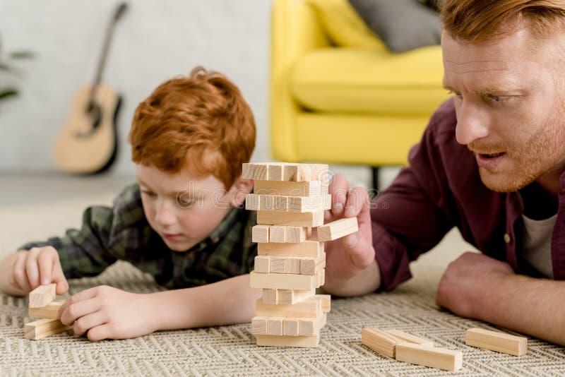 被集中的父亲和儿子大厦塔播种的射击从木块的 库存照片