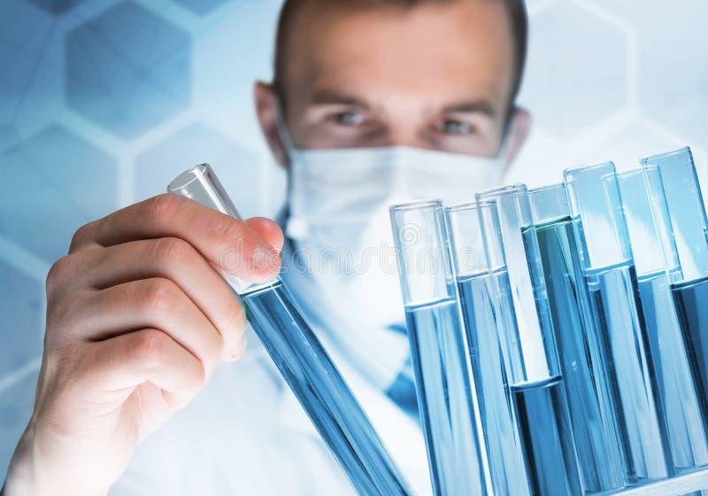 被集中的男性科学家画象与试剂一起使用在实验室 图库摄影