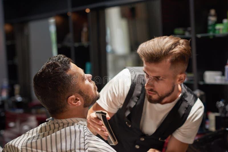 被集中的男性美发师在手上的拿着整理者 免版税图库摄影
