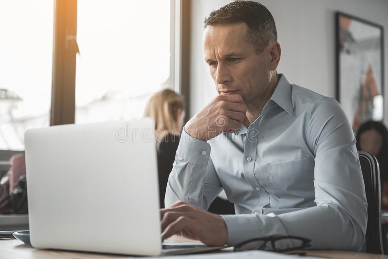 被集中的男性观看在膝上型计算机 免版税库存图片