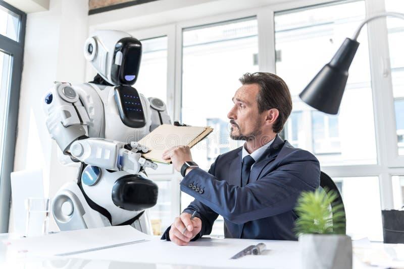被集中的确信的成熟人与机器人一起使用 免版税图库摄影