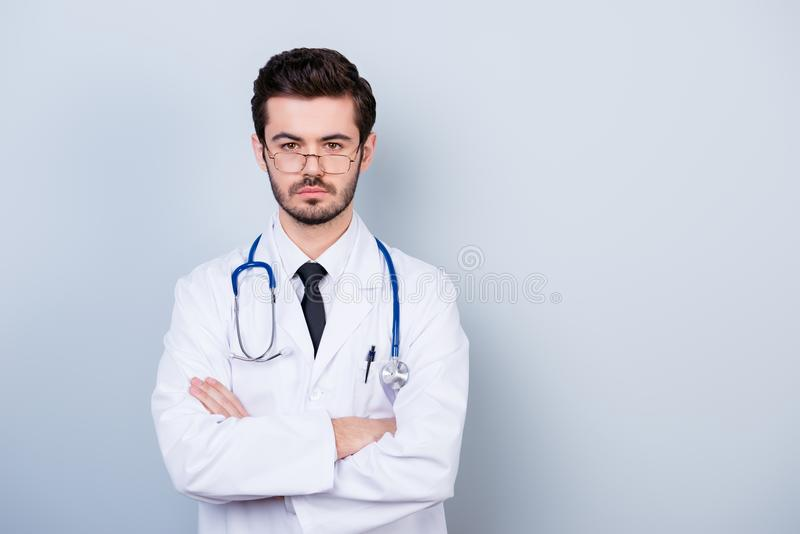 被集中的重视的医生画象站立wi的白色外套的 免版税库存图片