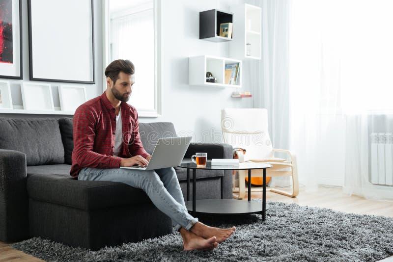 被集中的年轻人坐沙发使用便携式计算机 免版税库存照片