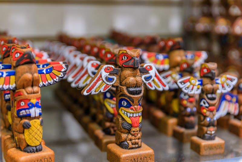 被雕刻的木第一个国家当地美洲印第安人标识杆纪念品在旅游商店在温哥华加拿大 免版税库存照片