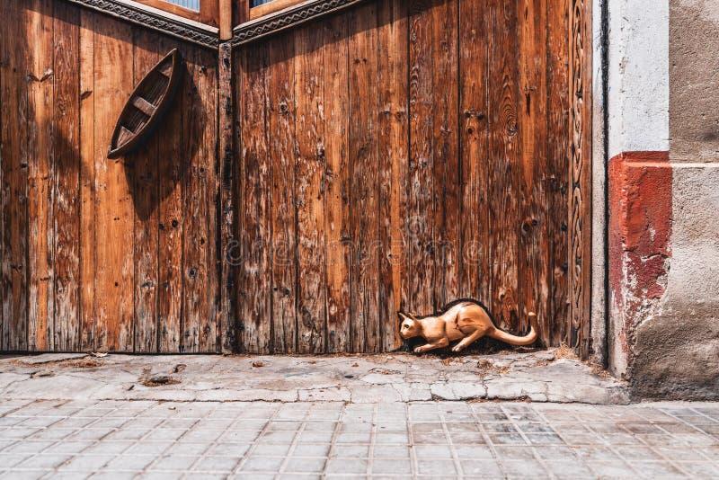 被雕刻的猫和小船在木门外面 免版税库存照片