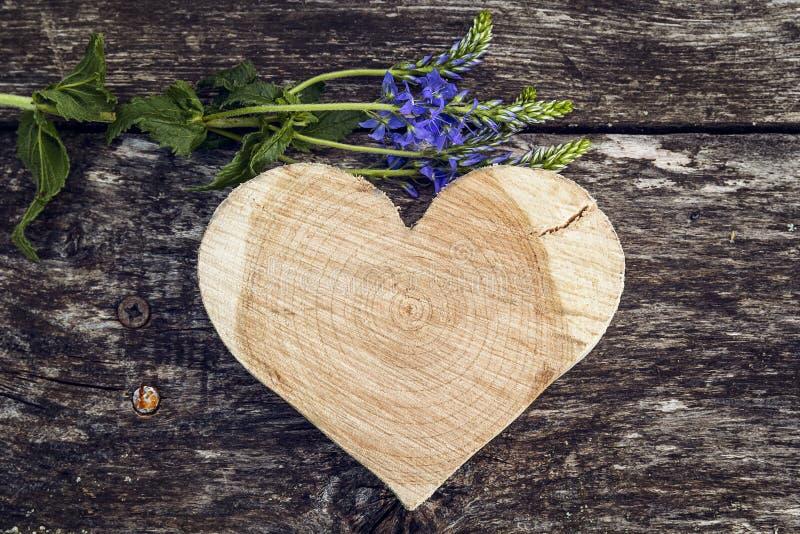 被雕刻的木心脏和蓝色花在老委员会背景  库存图片
