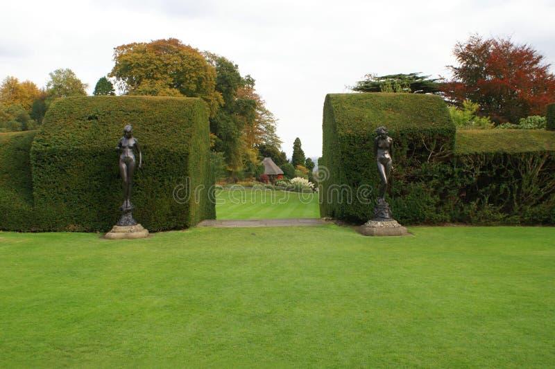 被雕刻的树篱和妇女雕象庭院入口  免版税库存照片