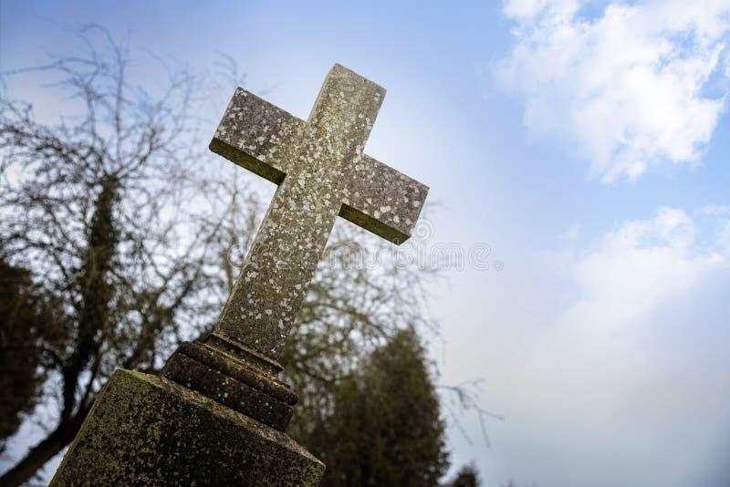 被风化的石十字架或墓碑反对蓝天, memori 免版税库存图片