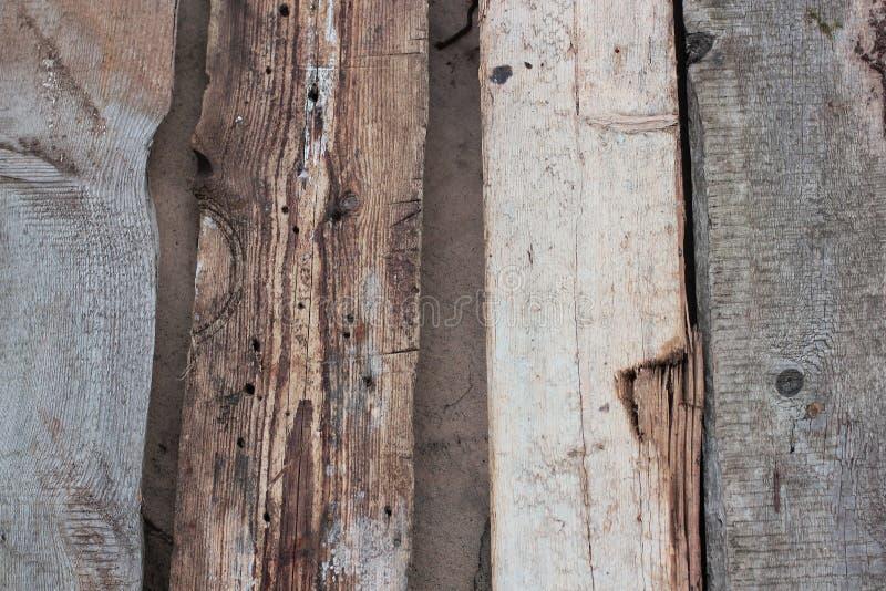 被风化的老木墙壁细节 有一起被钉牢的knotholes和粗面的简单的灰色委员会 室外 背景 照片 库存照片