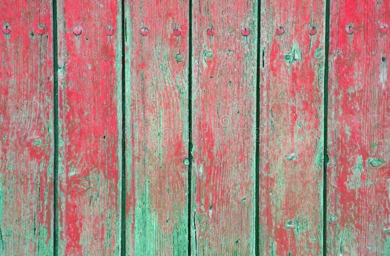 被风化的老木自然退色的绿色和红色绘了背景 库存照片