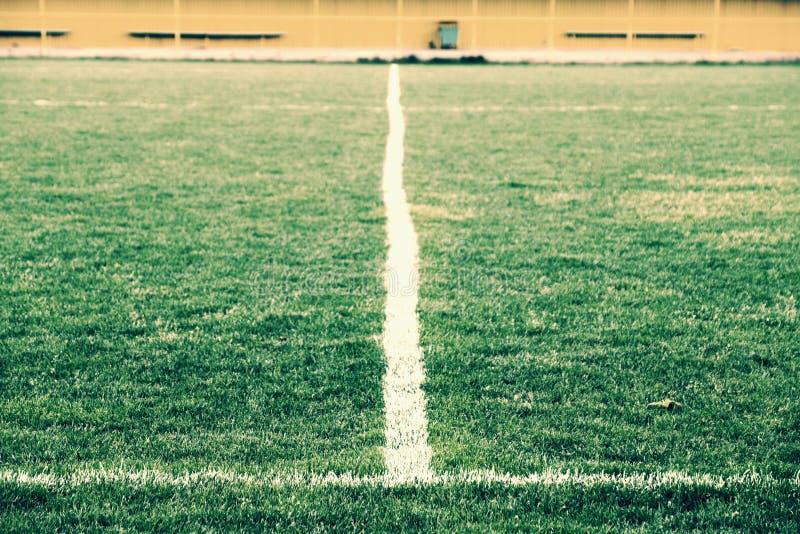 被绘的空白线路十字架在自然橄榄球草的 人为绿色草皮纹理 免版税库存照片