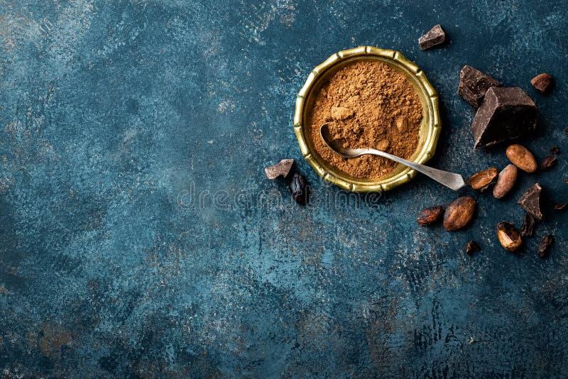 被击碎的可可粉、豆和黑暗的巧克力片,烹饪背景 免版税库存照片