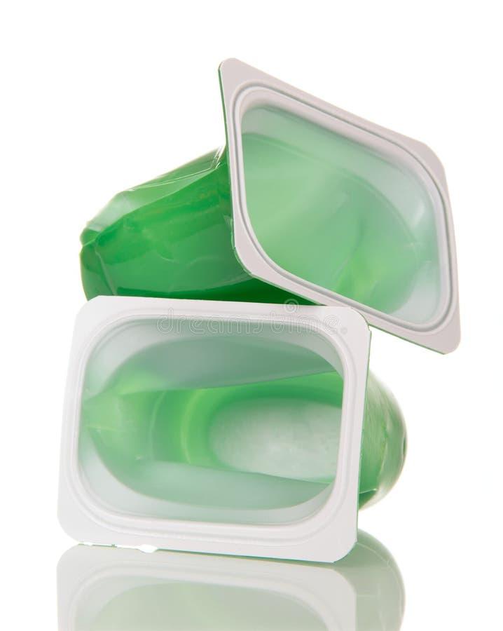 被击碎的塑料托起在白色背景隔绝的酸奶 库存图片