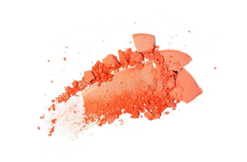 被击碎的橙色眼影膏污迹作为化妆产品样品的  免版税库存图片
