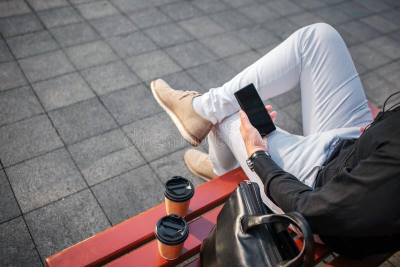 裁减观点的牛仔裤的人坐长凳外面和拿着黑电话 那里关于两个杯子和皮包 免版税库存图片