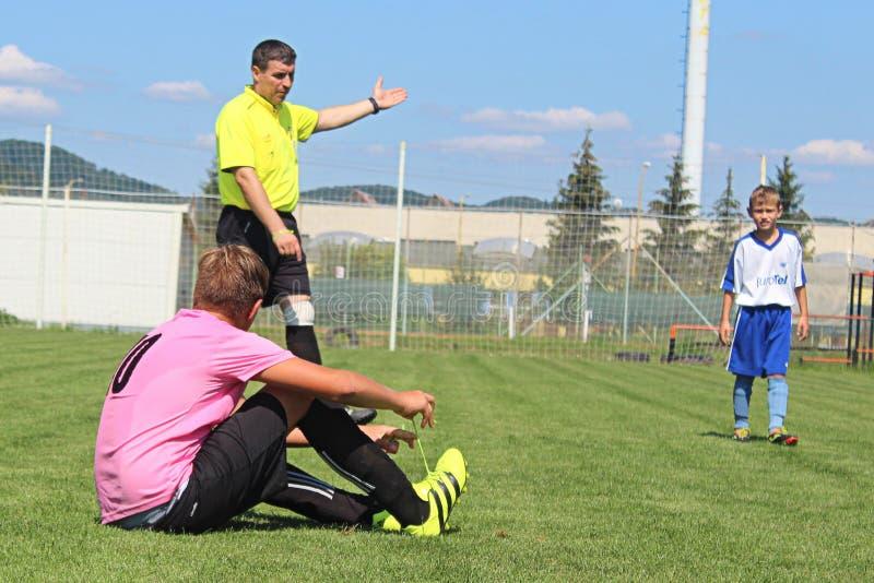 裁判员吹了口哨在一位年轻足球运动员的一不理智 免版税图库摄影