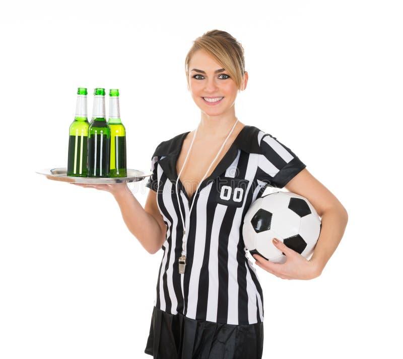 裁判员藏品饮料和橄榄球 免版税库存照片
