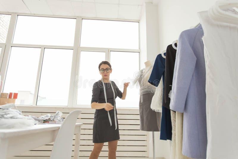 裁缝、时尚编辑、裁缝和人概念-在时髦的成套装备测量的材料打扮的设计师  免版税图库摄影