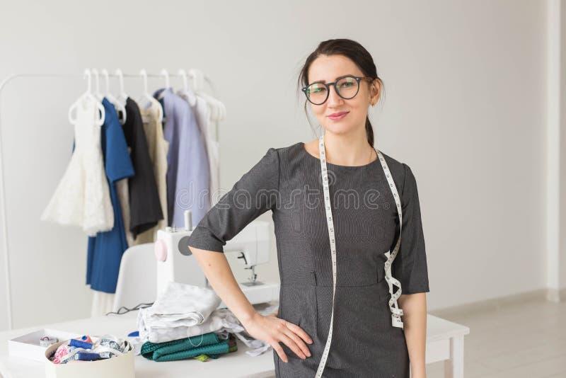 裁缝、时尚编辑和裁缝概念-在衣裳的年轻裁缝妇女折磨有礼服背景 免版税库存照片