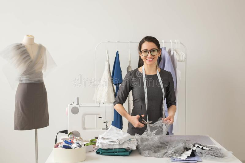 裁缝、时尚编辑和裁缝概念-年轻女人设计师切开美丽的轻的织品 库存图片