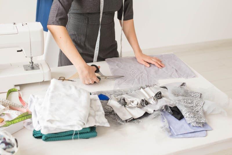 裁缝、时尚编辑和裁缝概念-年轻女人设计师,创造礼服的过程 库存图片